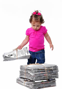Toddler with newspapers for recycling